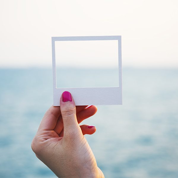 Hand holding perforated paper frame with ocean background